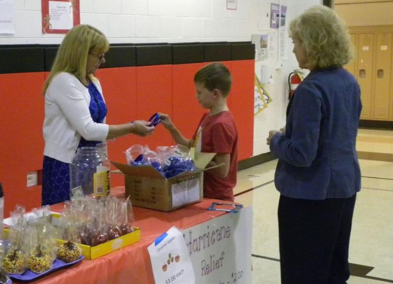 A student and adult purchasing a hurricane relief bracelet from a Memorial staff member.