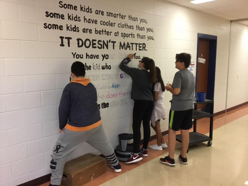 Art students work on a mural.