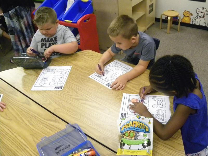 Kindergarten students work at a table.