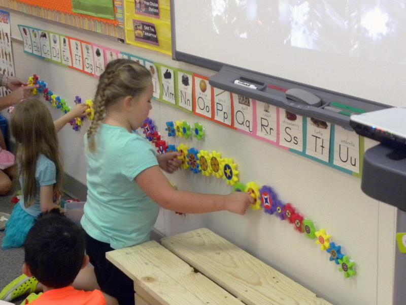 A kindergarten student uses gears to learn.