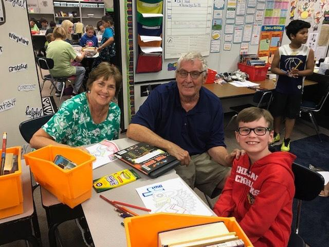 A student poses with his grandparents during special persons day.