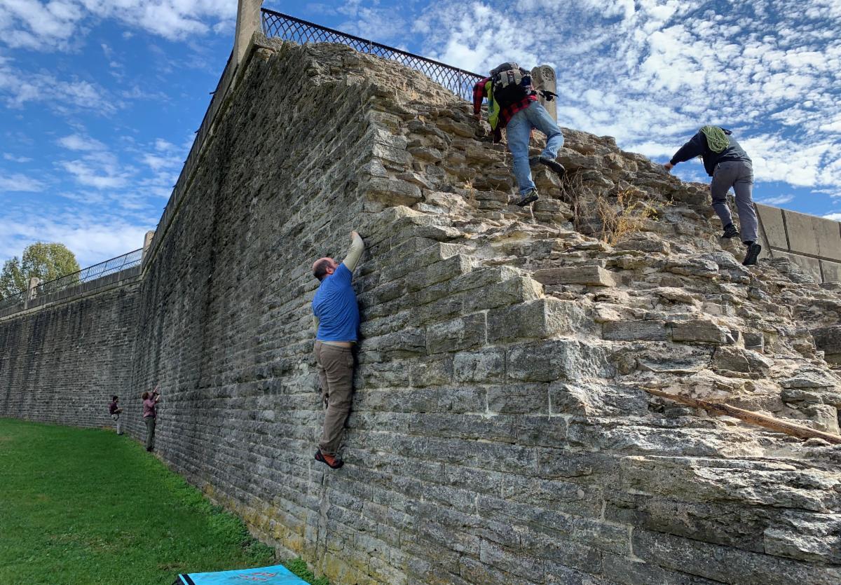 OCC volunteer climbing the Eden Park retaining wall
