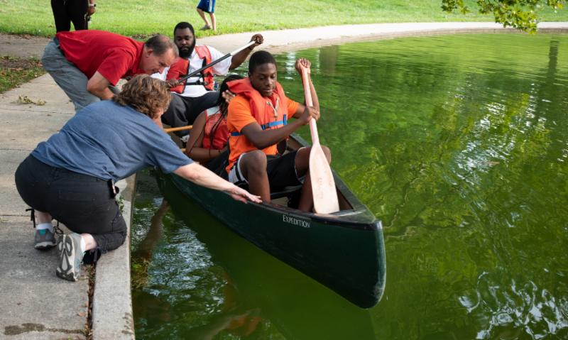 Parks staff help a family get into a canoe.