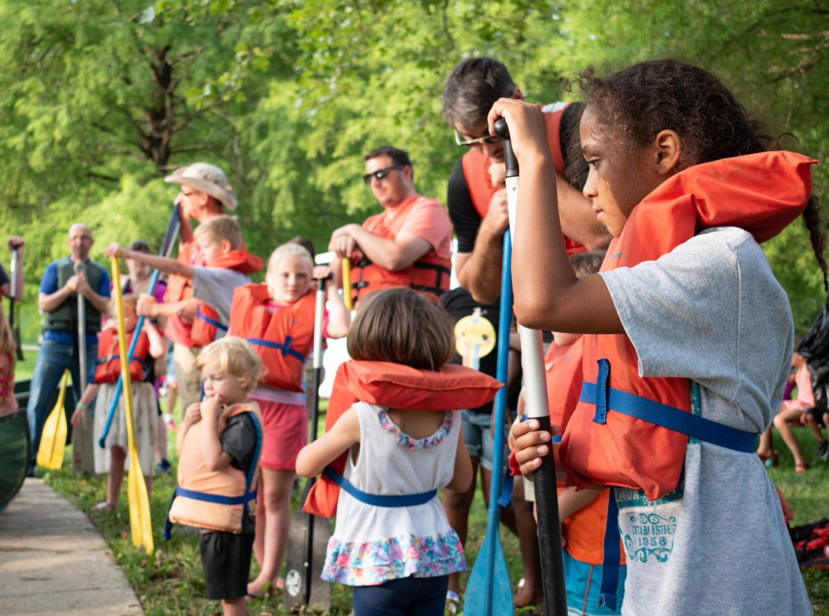People with life vests and canoe paddles