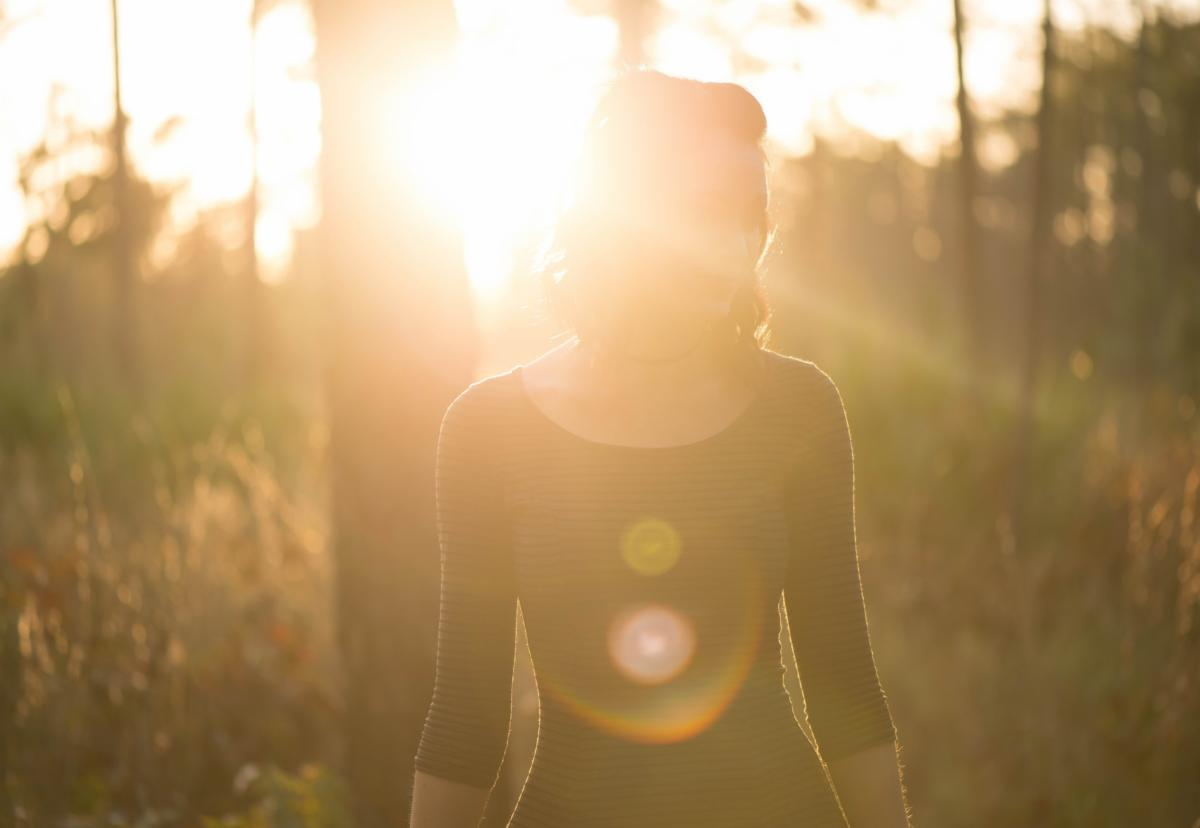 A woman stands in the sunshine in the woods