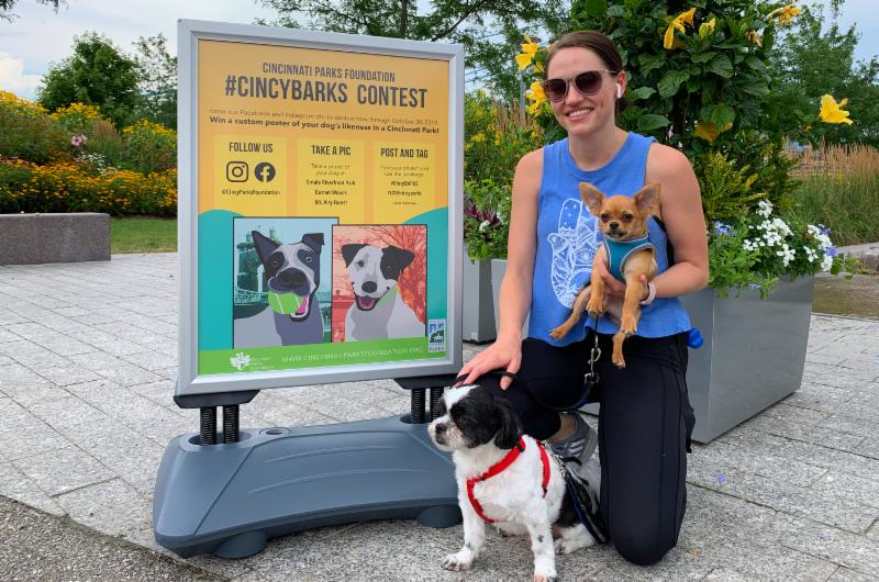 A woman with dogs and a #cincyBARKS contest poster.