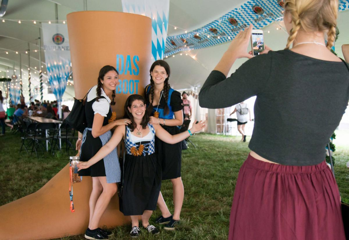 Women in traditional German clothes pose with a giant Das Boot.