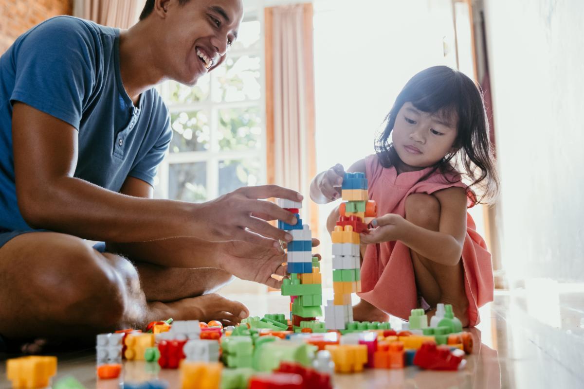 Dad and daughter stacking blocks