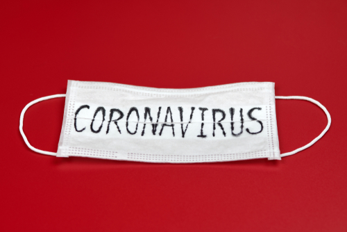 Novel coronavirus - 2019-nCoV_ WUHAN virus concept. Surgical mask protective mask with CORONAVIRUS text. Chinese coronavirus outbreak. Red background.