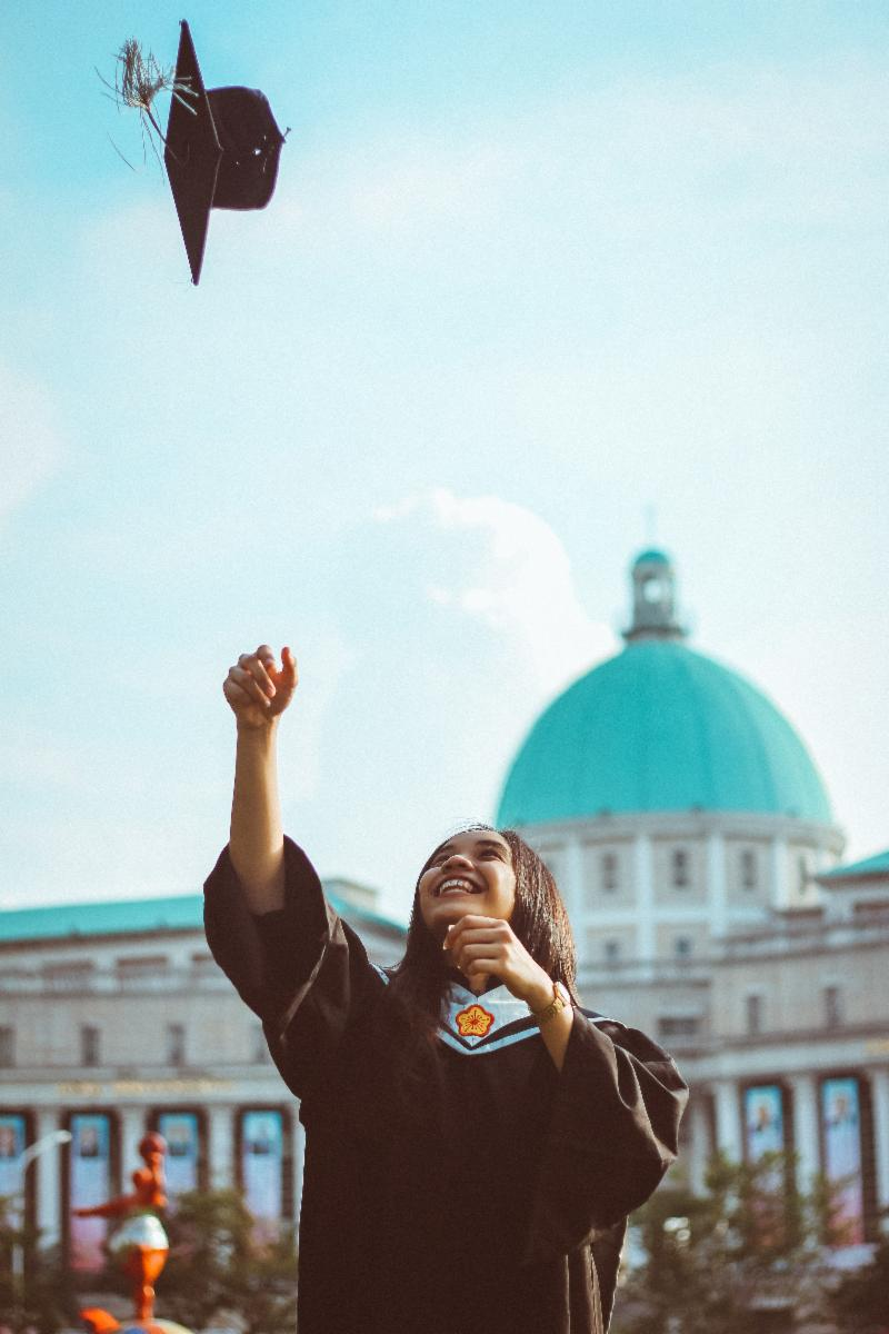 Woman throwing graduation cap up in air and smiling