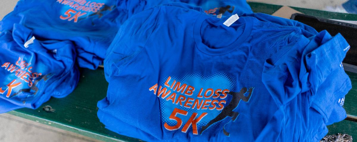 Limb Loss Awareness 5K t-shirts folded and in a pile on a table at the 2019 event.