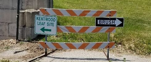 """Road closure barricade used to display arrow traffic-style signs that say """"brush"""" pointing to the right and """"Kentwood leaf site"""" pointing to the left."""
