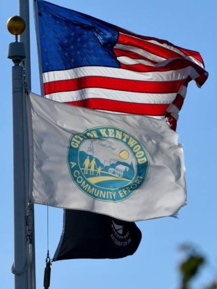 United States and City of Kentwood flags on a flagpole and flying open in the wind.