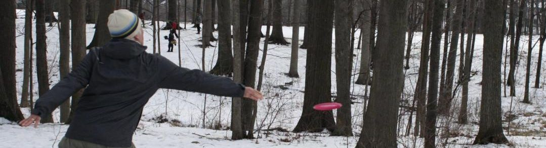 Disc golfer throws his disc toward a basket in winter.