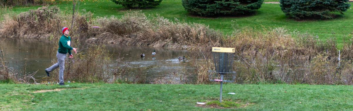 Disc golfer dressed for cool weather throws golf disc toward the basket at Old Farm Park.