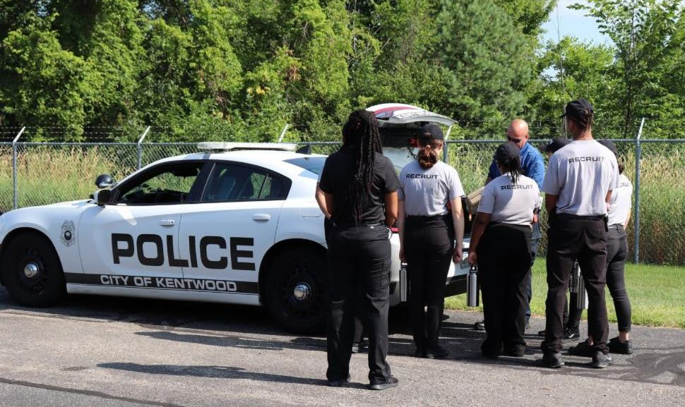An officer teaches Youth Police Academy participants about traffic stops next to a Kentwood police cruiser that is outside and has its trunk open.