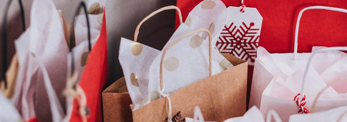 A group of brown, red and white holiday-themed paper presents/shopping bags.