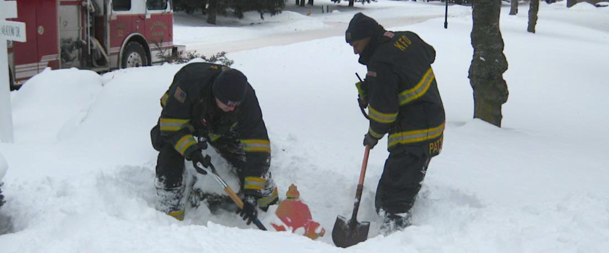 Firefighters shoveling snow aware from a fire hydrant in winter