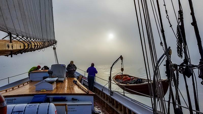 Looking aft from midships at sun barely visible through blanket of fog
