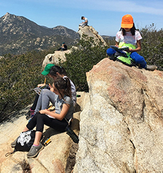kids at camp on large rock writing in journals