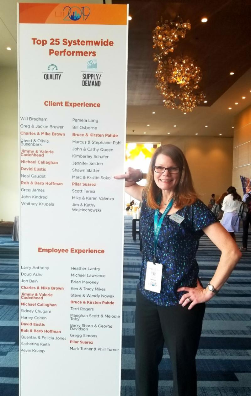 Owner Kristin Sokol points out her and her husband Marc's names on the Top 25 Systemwide Performers banner