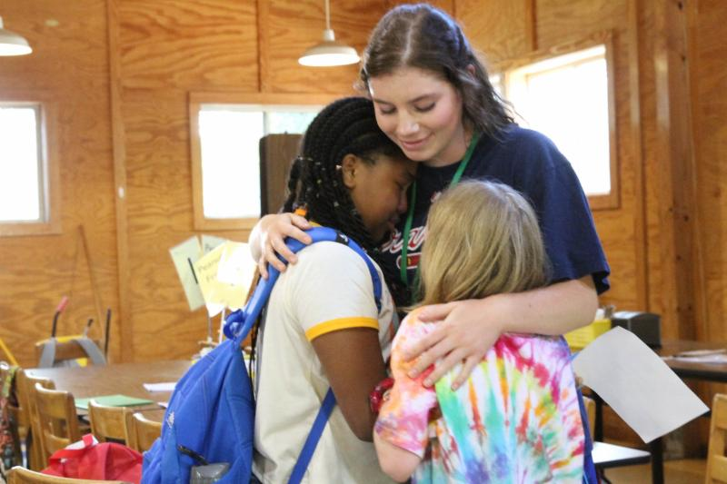A camp counselor hugs two campers.