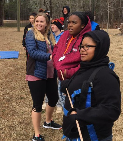 Campers smile as they hold a rope for tug of war.