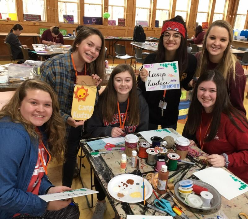 Campers smile to the camera during an arts and crafts session at the 2018 Teen Retreat.