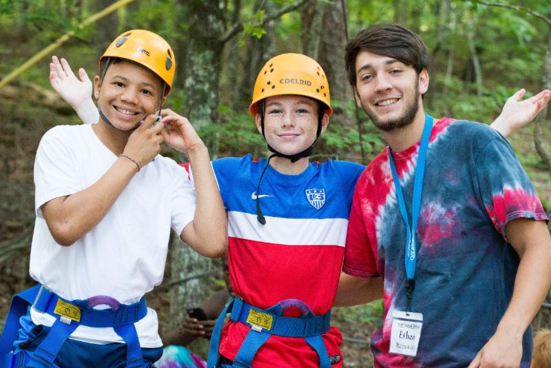 Three campers smile and pose for the camera at the Teen Retreat