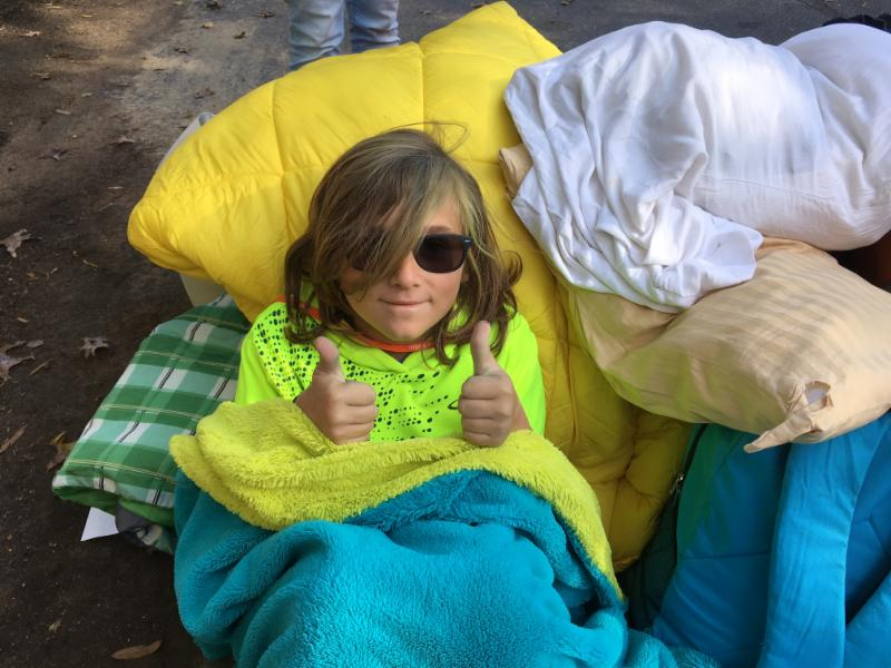 A child smiles and gives a thumbs up at Fall Family Camp.