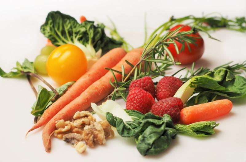 Assorted fruits and vegetables, including carrots, strawberries, and kale.