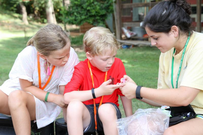 A Camp Kudzu volunteer helps campers check their bg levels.