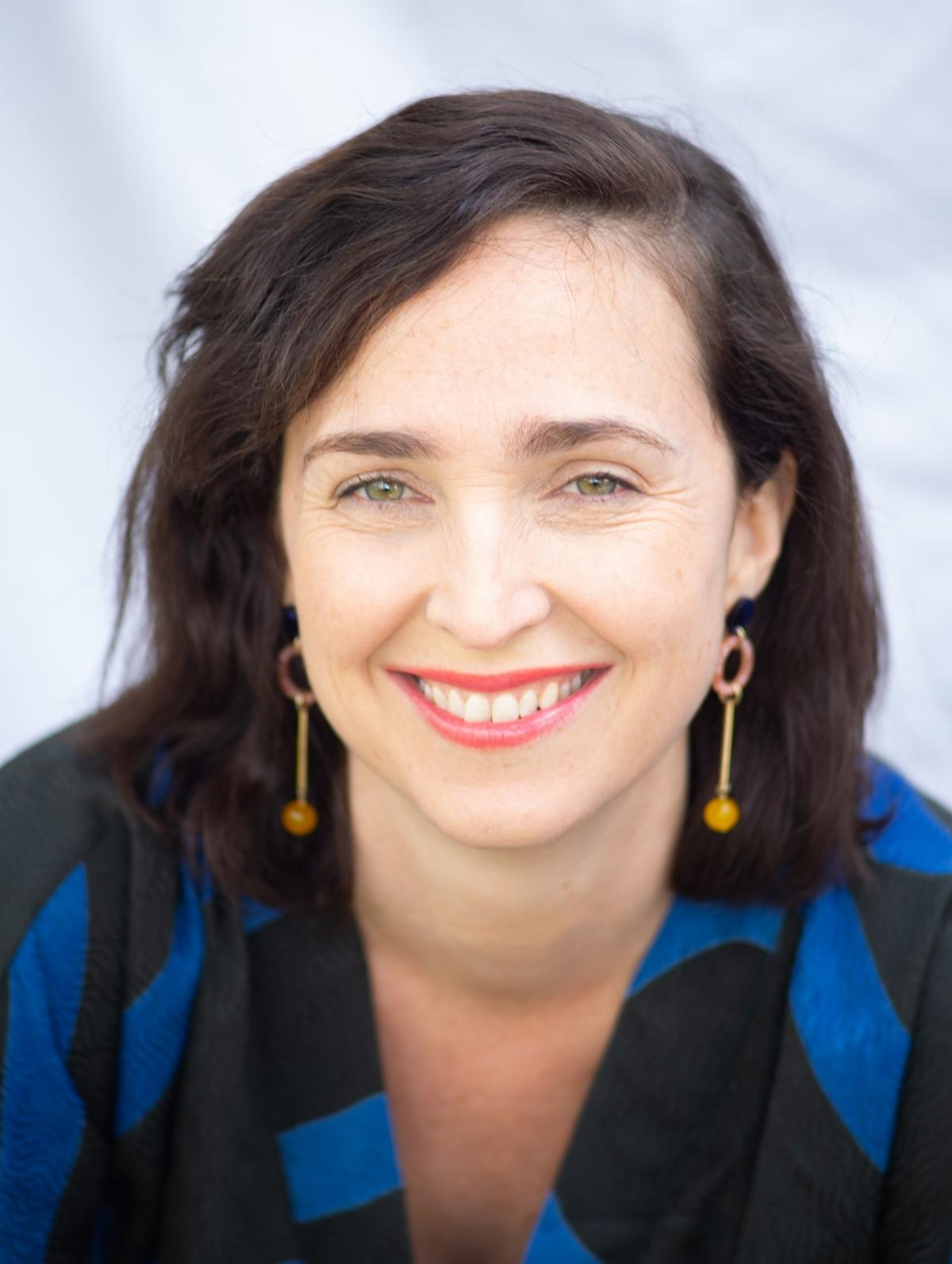 Woman smiling in blue and black blouse. Gold earrings. Colleen Houston.