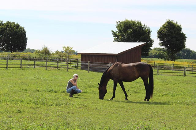Woman and horse in pasture