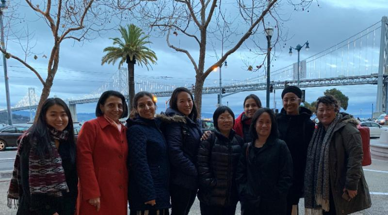 Photo of 9 staff at API-GBV standing in front of the Bay Bridge in San Francisco