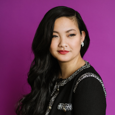 Headshot of a young East Asian woman against purple background