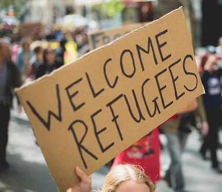 Closeup of a cardboard sign held up at a rally. Written on the sign: WELCOME REFUGEES