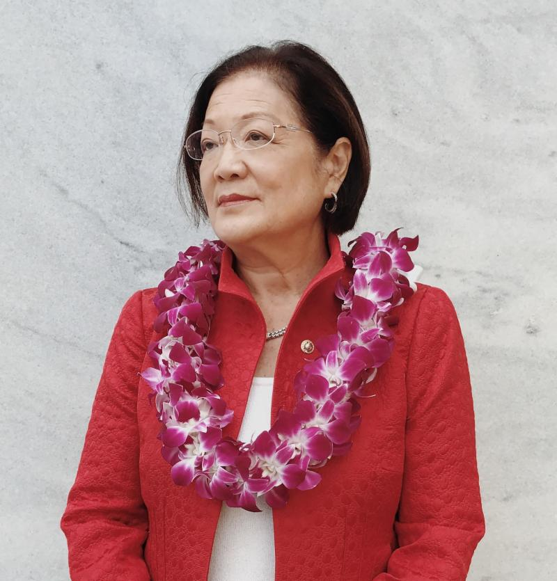 Photo of Mazie Hirono/A middl-aged East Asian woman wearing a red blazer and a lei