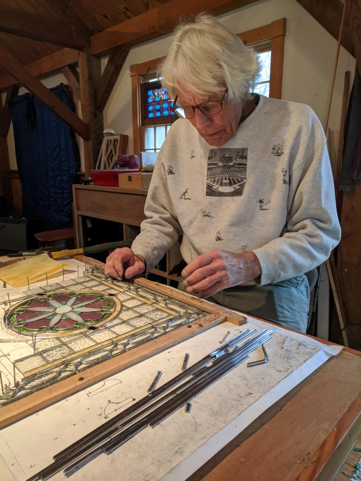 Photo of James Morgan working on stained glass