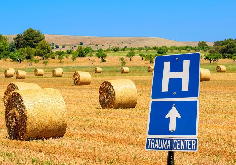 Blue hospital direction sign in the foreground with open fields with round hay bales in the background