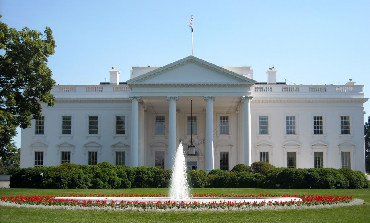 View of White House with water fountain in foreground surrounded by red and white flowers.