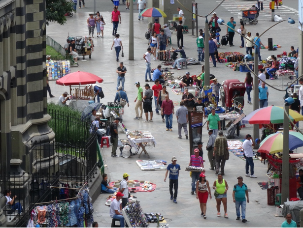 Busy urban street with a multistory building on the far left, many street vendors with stalls seated around, and people walking around