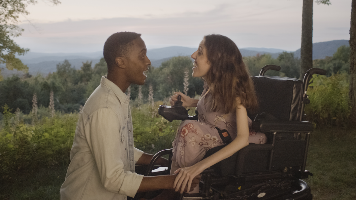 The romantic leads of the film in the forefront against trees and mountains in the middle of a duet.