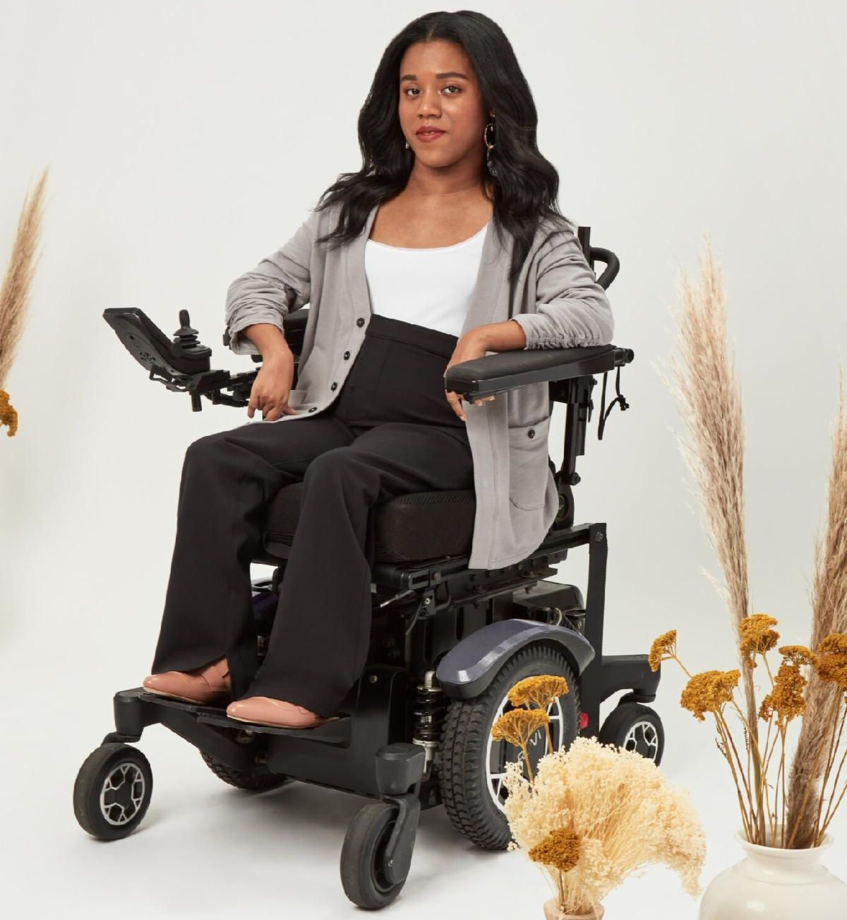 Woman with dark hair with black pants, white top, and grey sweater in a power wheelchair,