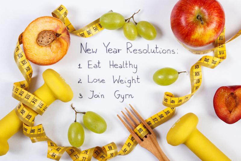 New year resolutions or goals on white background fresh fruits dumbbells and tape measure with wooden fork healthy food and lifestyle