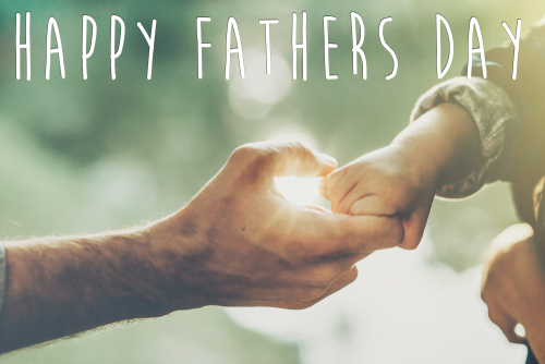 happy father s day text_ greeting card concept. father and little son holding hands in sunlight in summer forest. Trust_ care and parenting family concept. fathers day. road to life.