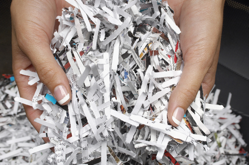Closeup of female hands with shredded papers