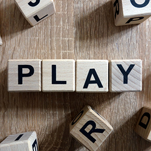Wooden letter blocks spell out PLAY on a wooden surface.  Other letter blocks are scattered around.