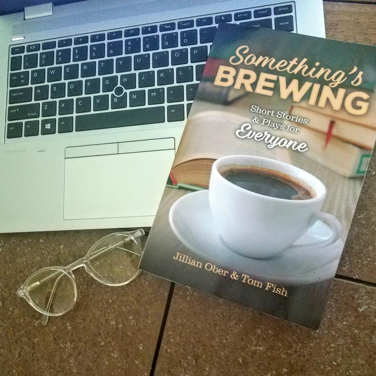 A book titled Something's Brewing: Stories and Plays for Everyone by Jillian Ober & Tom Fish sits atop a laptop keyboard.  A pair of glasses is next to the book.