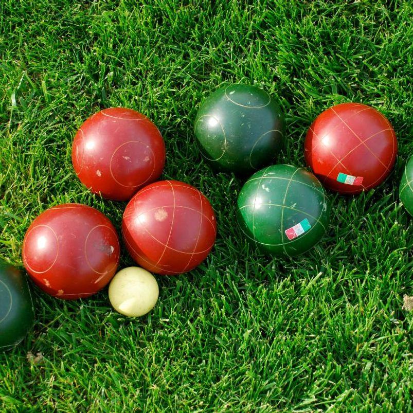 Bocce balls lie in a field of green grass